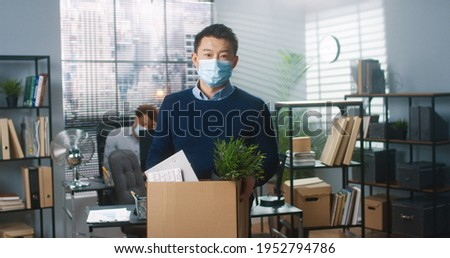 Portrait of Asian male worker in medical mask standing in cabinet holding carton box with his stuff and looking at camera with sad face, fired employee at office, last day at work, employment concept Royalty-Free Stock Photo #1952794786
