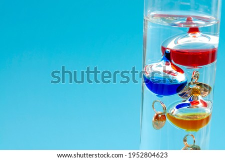 Temperature measurement instruments, educational tools, meteorology concept with Galileo thermometer made of coloured glass balls in a water filled cylinder isolated on blue background with copy space