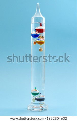 Temperature measurement instruments, educational tools, meteorology concept with Galileo thermometer made of coloured glass balls in a water filled cylinder isolated on blue background