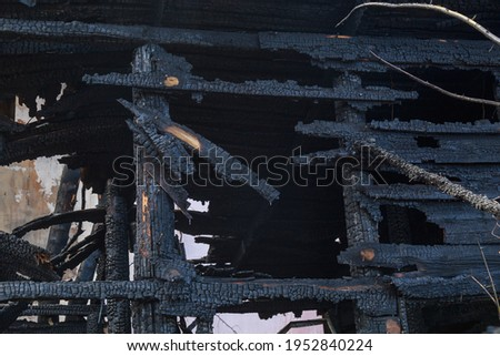 The aftermath of a fire in old wooden sheds. Background Royalty-Free Stock Photo #1952840224