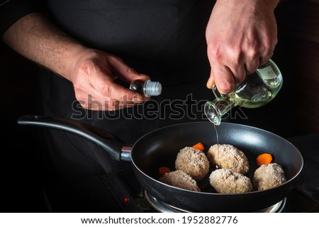 Cooking beef cutlets in a grill pan with the hands of a chef on a black background for copying the space text restaurant menu. Chef adds oil