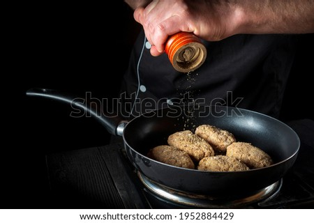 Cooking cutlets on grill pan by chef hands on black background for copy space text restaurant menu. The chef adds pepper