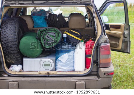 Suitcases and bags in trunk of car ready to depart for holidays. Moving boxes and suitcases in trunk of car, outdoors. trip, travel, sea. car on the beach with sea on background Royalty-Free Stock Photo #1952899651
