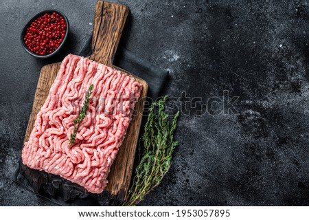 Ground chicken or turkey raw meat on wooden board. Black background. Top View. Copy space Royalty-Free Stock Photo #1953057895