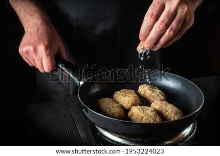 Cooking cutlets on grill pan by chef hands on black background for copy space text restaurant menu. The chef adds salt