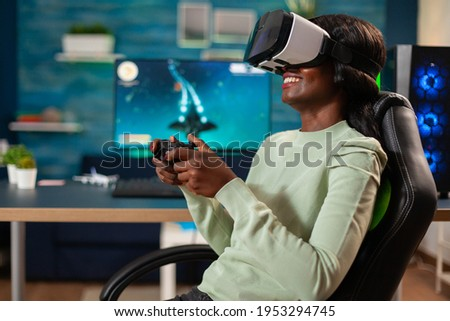 African gamer e-sports with vr sitting in chair using wireless controler. Virtual space shooter video game championship in cyberspace, esports player performing on pc during gaming tournament. Royalty-Free Stock Photo #1953294745