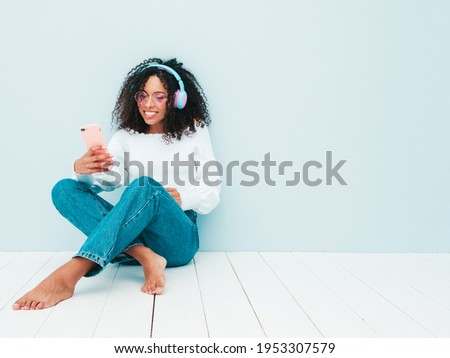 Beautiful black woman with afro curls hairstyle.Smiling model in sweater and jeans.Sexy carefree female listening music in wireless headphones.Sitting in studio near light blue wall.Taking selfie