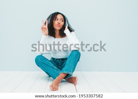 Beautiful black woman with afro curls hairstyle.Smiling model in sweater and jeans.Sexy carefree female listening music in wireless headphones.Sitting in studio near light blue wall.Shows peace sign