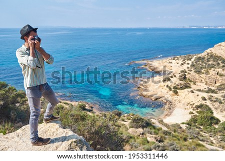 A romantic young man takes photos with his film camera in a cove of the Mediterranean Sea in a tourist area where the sea has beautiful colors