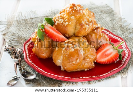 Profiteroles with nuts and strawberries over light background #195335111