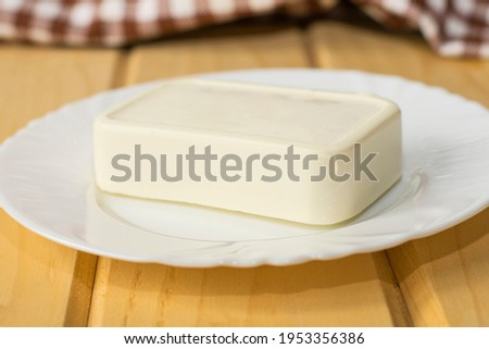 A block of traditional Greek feta cheese on a white plate close-up. Shallow depth of field. Royalty-Free Stock Photo #1953356386