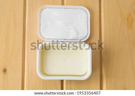 Traditional Greek feta cheese in brine on a wooden table. Feta cheese in an open package on a table. Top view. Royalty-Free Stock Photo #1953356407