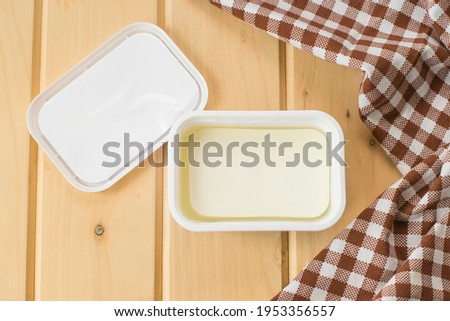 Traditional Greek feta cheese packaged in brine on a wooden table with a tea towel. Top view. Royalty-Free Stock Photo #1953356557