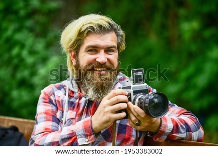 Real joy. bearded man hipster take photo. photo shooting outdoor. brutal man traveler with retro camera. photography in modern life. travel tips. professional photographer use vintage camera