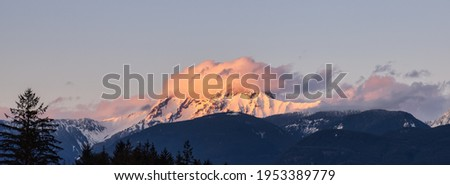 Panoramic View of Canadian Mountain Landscape covered in Clouds. Colorful Sunset Sky. Mt Garibaldi in Squamish, British Columbia, Canada. Nature Background Panorama Royalty-Free Stock Photo #1953389779