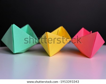 multicolored paper boats on a white background