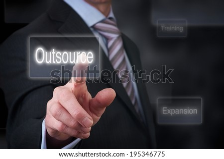 A businessman Pointing to a business outsourcing button on a clear screen. #195346775