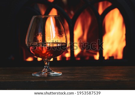 A glass with cognac in front of the fireplace in the cozy living room. Royalty-Free Stock Photo #1953587539