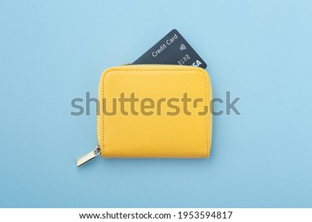 Credit card in yellow wallet on blue background, top view Royalty-Free Stock Photo #1953594817