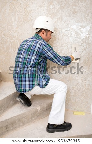 Builder-repairman plasterer in a protective helmet while repairing applies decorative plaster, pattern on the wall, sitting Royalty-Free Stock Photo #1953679315