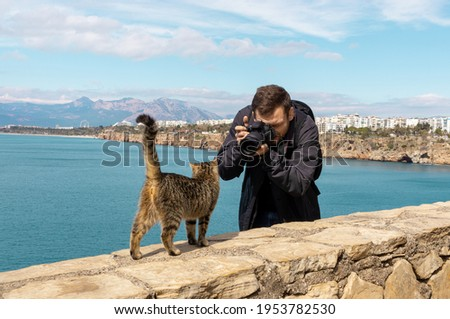 Young man wearing black coat taking photo of street homeless cat. Street photographer and cat. Lifestyle of photographers. Traveler with lens camera in Turkey.