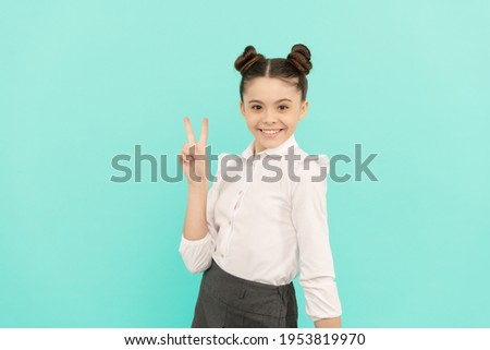 Peace maker. School age kid show V sign. Happy kid blue background. Basic education. Back to school. September 1. Knowledge day. Happy childhood.