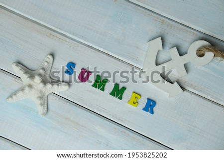 word summer is made up of volumetric colored letters on a light blue wooden background, white starfish, anchor, summer time concept, vacation time, travel, boat trip, beach impressions