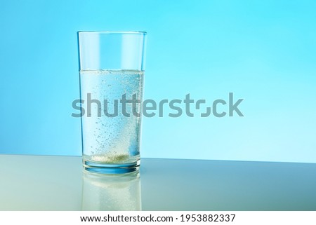 dissolving pill dissolves in water on colored background. a glass of water and an effervescent paracetamol tablet. the medicine tablet dissolves in a glass of water