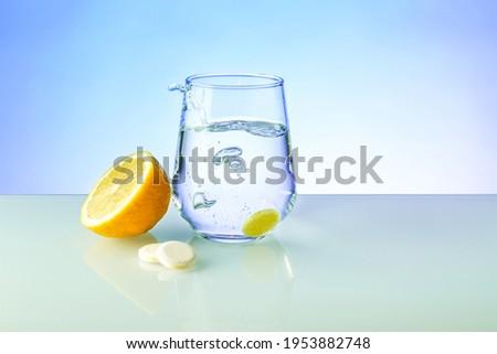 effervescent vitamin C tablet dissolves in water. a glass of water, effervescent tablet and lemon fruit on blue background. vitamin C concept