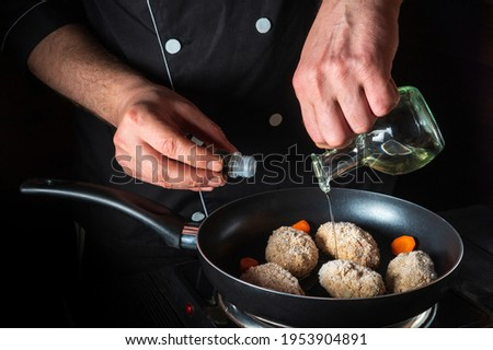 Cooking beef cutlets in a grill pan with the hands of a chef on a black background for copying the space text restaurant menu. Chef or cook adds oil
