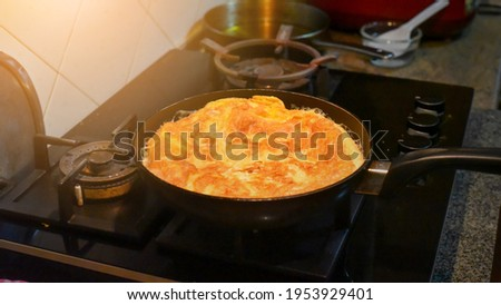 Cooking Eggs pancakes in a frying pan, pan on top of the gas stove. Picture have noise, Soft focus.