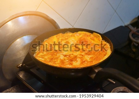 Cooking Eggs pancakes in a frying pan, closeup. Pan on top of the gas stove. Picture have noise, Soft focus.2.jpg