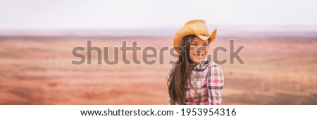 Cowgirl woman smiling happy on country farm landscape wearing cowboy hat. Banner of young multiracial Asian American girl in panoramic countryside.