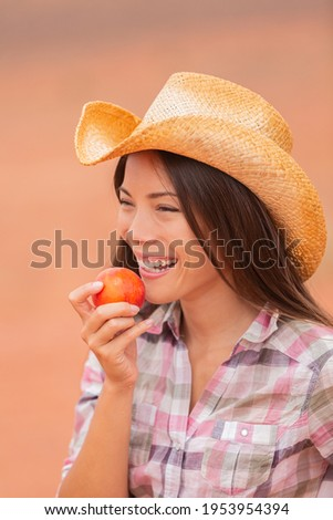 USA cowgirl eating peach nectarine fruit smiling wearing cowboy hat at outdoor country farm . Healthy food farmers market with beautiful young mixed race Caucasian Asian model .