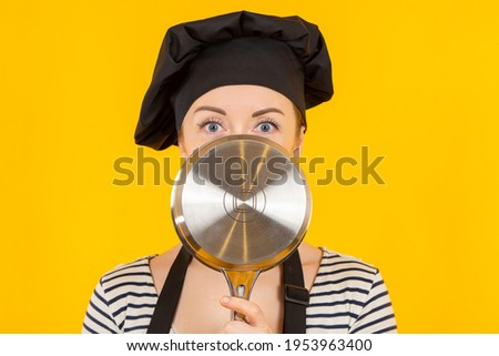 Cook hides his face behind a saucepan. Portrait of a female chef with a saucepan in front of her face. Cook tries to hide. Girl chef on a yellow background. Cook in a black chef's hat. Royalty-Free Stock Photo #1953963400