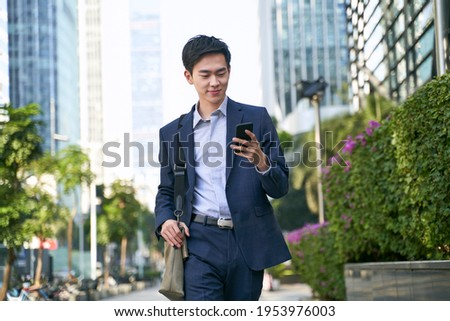 young asian businessman looking at messages on cellphone while walking in the street in downtown of modern city Royalty-Free Stock Photo #1953976003