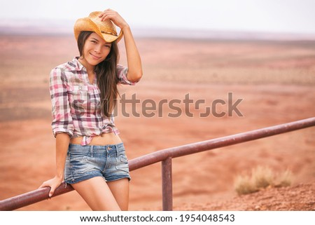 Cowgirl woman smiling at camera holding hat as greeting gesture happy on country farm landscape wearing cowboy western shirt and jeans. Young multiracial Asian American girl in desert countryside.