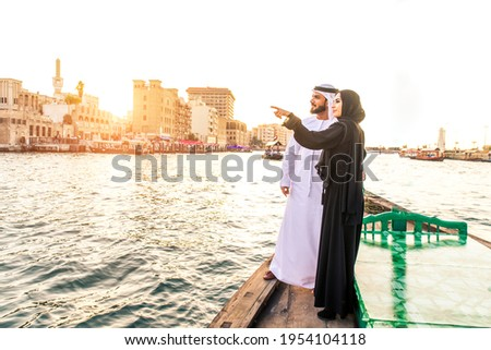 Arabian married couple visiting Dubai on abra boat - Two people on traditional boat at Dubai creek Royalty-Free Stock Photo #1954104118