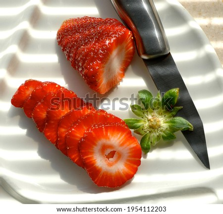 Stock photo of a dish with a cut strawberry and a strawberry with a knife on the side and rays of light illuminating. Food and lifestyle