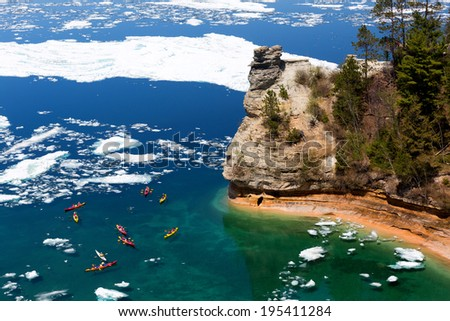 Kayaks maneuver through ice floes to view Miners Castle on Lake Superior. Late ice breakup created unusual ice formations at Pictured Rocks National Lakeshore in the Upper Peninsula of Michigan