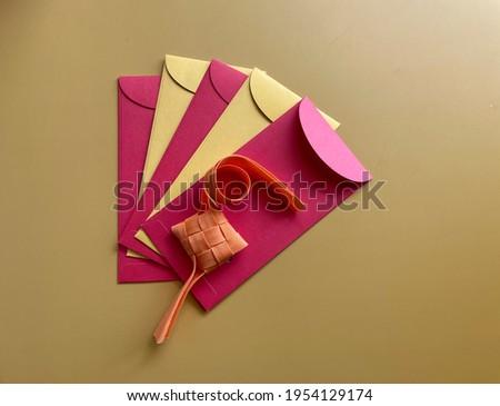 Colorful money packets or 'Sampul Raya and ribbon ketupat for Muslim Eid celebration on colored background. Hari Raya concept Royalty-Free Stock Photo #1954129174