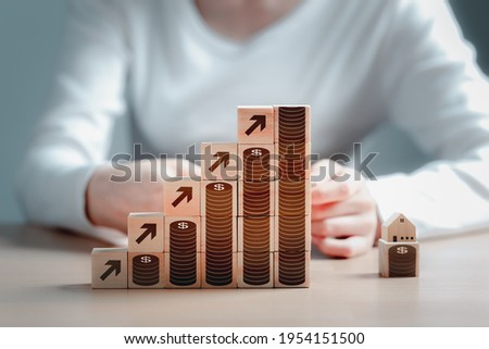 Woman is building blocks of wood and dollar coins as the steps leading to the house. Loan or save money for buy a house and real estate concept.