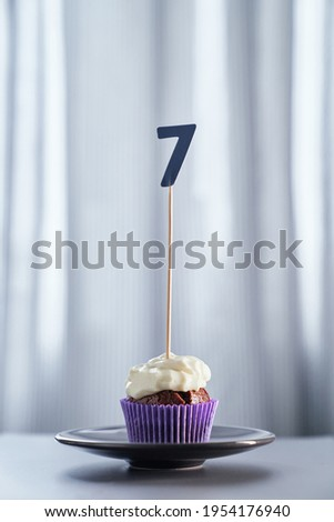 Minimalistic birthday or anniversary concept. Homemade chocolate birthday cupcake with creamy topping and number 7 seven on black plate and bright background. High quality vertical image