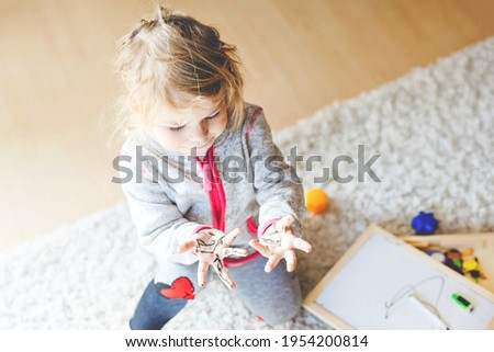 Sad crying toddler girl learning painting with felt tip pens. Little baby child drawing on hands and clothes. Angry child in hysteric crisis as parents scold with daughter for dirty hands