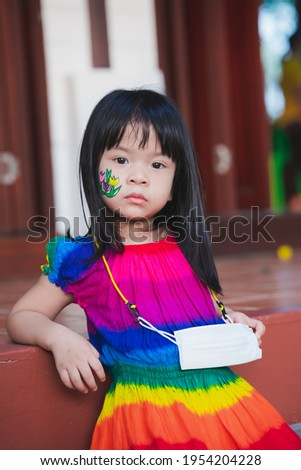 Portrait upset child leaning against wooden battens look at camera. Girl wear colorful dress. On her face is painting flower cartoon with watercolor. Easter or Halloween day. Kid hold mask around neck