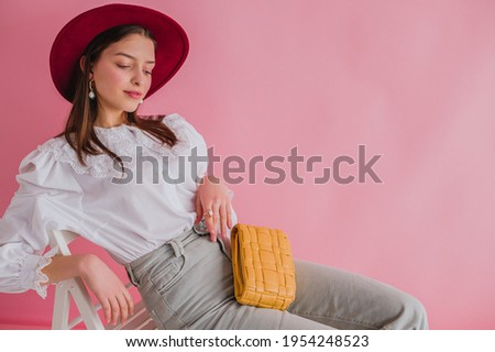 Elegant fashionable woman wearing trendy white vintage cotton shirt with lace collar, stylish marsala color hat,  with yellow padded leather bag, posing on pink background. Copy, empty space for text