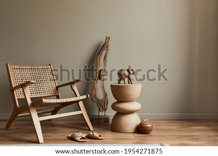 Stlish interior of living room with rattan armchair, wooden stool, elephant figure and decoration in modern home decor. Copy space. Template. Royalty-Free Stock Photo #1954271875
