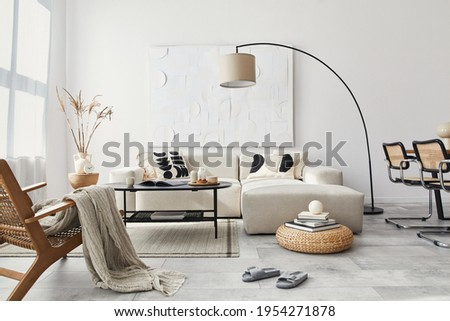 Domestic interior of living room with design modular sofa, black coffee table, lamp, armchair, decoration, art paintings and elegant personal accessories in modern home decor. Template. Royalty-Free Stock Photo #1954271878