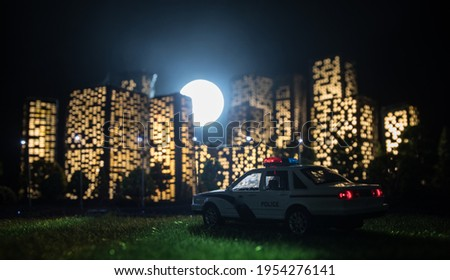 Cartoon style city buildings. Realistic city building miniatures with lights. background. Miniature police standing with City lights on the background. Selective focus