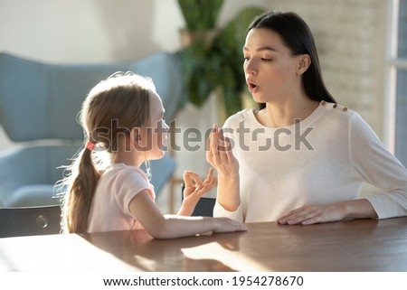 Caring young Caucasian mother teach small 7s daughter articulation exercised at lesson at home. Mom or teacher and little girl child learn pronouncing sounds together. Pronunciation concept. Royalty-Free Stock Photo #1954278670